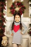 Menina que está perto da porta com festão do Natal Fotografia de Stock Royalty Free