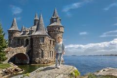 Menina que está em uma rocha grande perto do lago contra o castelo velho do vintage Fotografia de Stock Royalty Free