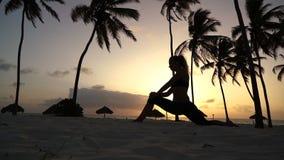 Menina que estica a ioga na manhã nas palmeiras no alvorecer filme