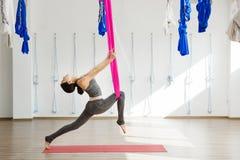 Menina que estica os pés com ajuda da rede Ioga aérea do exercício Fotografia de Stock