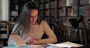 Menina que estuda e que datilografa na tabuleta na biblioteca filme