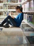 Menina que estuda na biblioteca Fotos de Stock