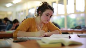 Menina que estuda na biblioteca vídeos de arquivo