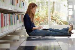 Menina que estuda no assoalho na biblioteca Foto de Stock Royalty Free
