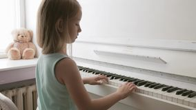 Menina que estuda para jogar em casa o piano Crian?a pr?-escolar que tem o divertimento com aprendizagem jogar o instrumento de m vídeos de arquivo