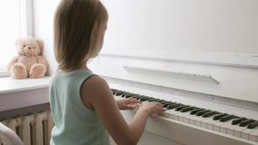 Menina que estuda para jogar em casa o piano Crian?a pr?-escolar que tem o divertimento com aprendizagem jogar o instrumento de m video estoque