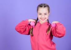 menina que exercita com dumbbell Fundo violeta do peso pequeno da posse da crian?a Exerc?cios do peso do novato Ostente para fotografia de stock royalty free