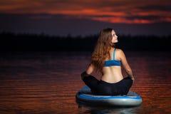 Menina que exercita a ioga no paddleboard no por do sol no lago cênico Velke Darko imagens de stock