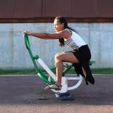 Menina que exercita na máquina do treinamento para o halterofilismo Foto de Stock