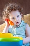 Menina que fala em um telefone do brinquedo imagens de stock