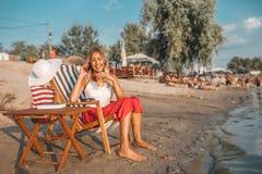Menina que fala em um telefone e em um suco bebendo na praia fotos de stock royalty free