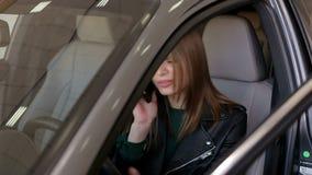 Menina que fala no telefone ao conduzir um carro novo, está feliz comprar um carro novo video estoque