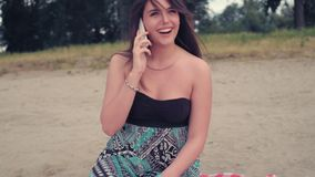 Menina que fala no telefone ao sentar-se na praia vídeos de arquivo