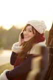 Menina que fala no telefone celular no banco no parque Fotografia de Stock Royalty Free