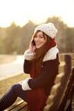 Menina que fala no telefone celular no banco no parque Foto de Stock Royalty Free