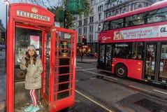 Menina que fala no telefone na cabine de telefone em Londres imagens de stock