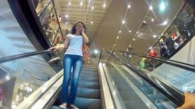 Menina que fala no telefone na escada rolante em uma alameda filme