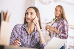Menina que fala no telefone no escritório Imagens de Stock Royalty Free