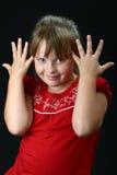 Menina que faz as orelhas de elefante com suas mãos no preto fotografia de stock