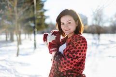 Menina que faz a bola de neve e que smiing in camera no inverno Fotografia de Stock