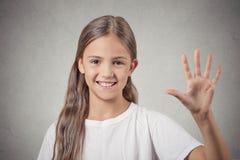 A menina que faz cinco vezes assina o gesto com mão Foto de Stock