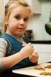Menina que faz cookies do pão-de-espécie para o Natal Fotografia de Stock Royalty Free
