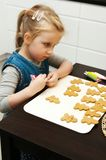 Menina que faz cookies do pão-de-espécie para o Natal Fotografia de Stock