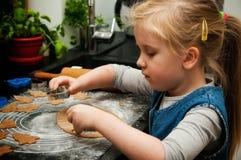 Menina que faz cookies do pão-de-espécie para o Natal Imagens de Stock Royalty Free