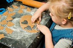 Menina que faz cookies do pão-de-espécie para o Natal Imagem de Stock Royalty Free