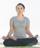 Menina que faz de pernas cruzadas a pose da ioga Fotos de Stock Royalty Free