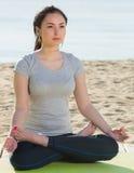 Menina que faz de pernas cruzadas a pose da ioga Imagem de Stock