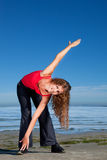 Menina que faz exercícios da manhã na praia Imagem de Stock