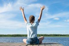 Menina que faz exercícios da manhã no lago em um dia agradável imagens de stock
