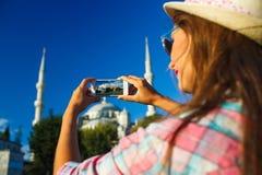Menina que faz a foto pelo smartphone perto da mesquita azul, Istan Fotos de Stock Royalty Free
