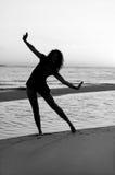 Menina que faz a ginástica na praia no por do sol Imagem de Stock