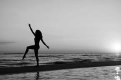 Menina que faz a ginástica na praia no por do sol Imagem de Stock Royalty Free