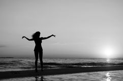 Menina que faz a ginástica na praia no por do sol Imagens de Stock Royalty Free