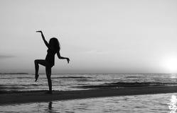 Menina que faz a ginástica na praia no por do sol Foto de Stock