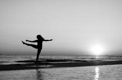 Menina que faz a ginástica na praia no por do sol Fotografia de Stock Royalty Free