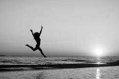Menina que faz a ginástica na praia no por do sol Imagens de Stock