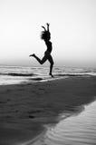 Menina que faz a ginástica na praia no por do sol Foto de Stock Royalty Free