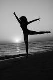 Menina que faz a ginástica na praia no por do sol Fotos de Stock