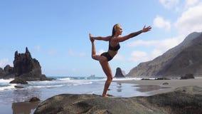 Menina que faz a ioga que equilibra em um pé que está em uma pedra Paz de espírito Estilo de vida saudável Equilíbrio e harmonia, vídeos de arquivo