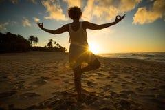 Menina que faz a ioga na praia no por do sol Imagem de Stock Royalty Free