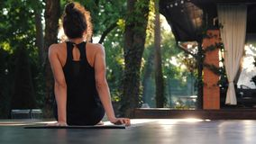 A menina que faz Koundinyasana, então jovem mulher fora da posição do asana e senta-se para baixo na esteira da ioga apenas Dar c video estoque