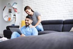 Menina que faz massagens o noivo em Sofa At Home Imagens de Stock