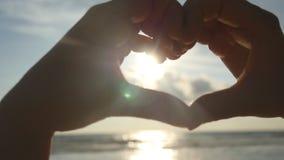Menina que faz o coração com suas mãos sobre o fundo do mar com por do sol dourado bonito Silhueta do braço fêmea no coração filme