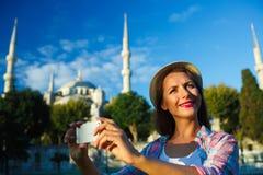Menina que faz o selfie pelo smartphone no fundo do Bl Imagens de Stock Royalty Free