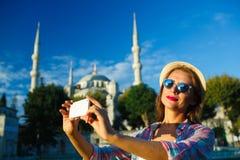 Menina que faz o selfie pelo smartphone no fundo do Bl Imagens de Stock