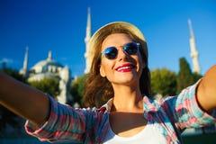Menina que faz o selfie pelo smartphone no fundo do Bl Fotografia de Stock Royalty Free